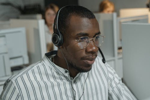 Man in White and Black Striped Button Up Shirt Wearing Black Headphones