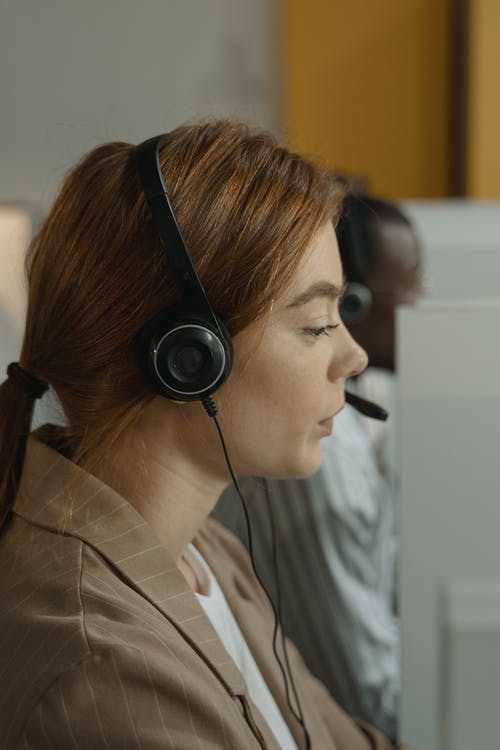 Woman in Brown Jacket Wearing Black Headphones