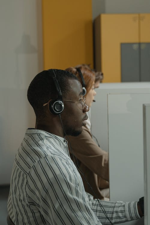 Man in White and Black Stripe Shirt Wearing Black Headphones