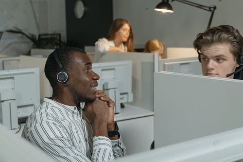 Man in White and Black Striped Shirt Wearing Headphones