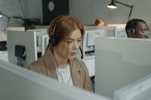 Woman in Brown Blazer Wearing Black Headphones
