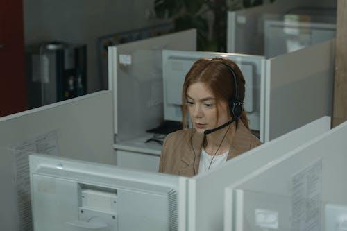 Woman in White Shirt Wearing Headphones