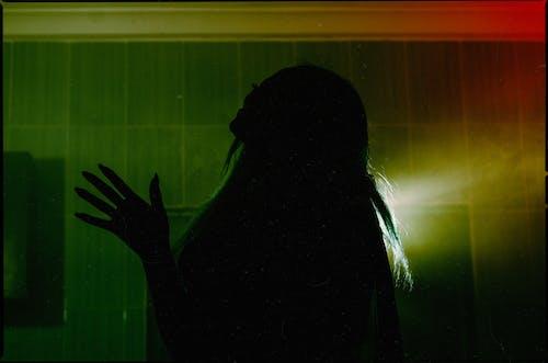 長長的頭髮站在黑暗的房間裡的女人的身影