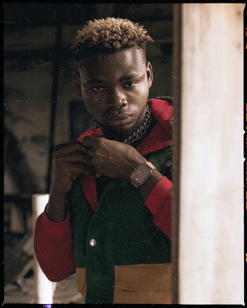 Focused black man touching lapel in grunge room