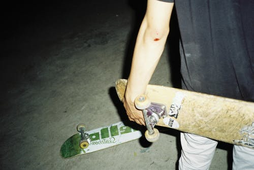 Person Holding Brown Skateboard Beside White and Green Skateboard