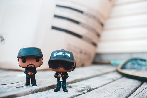 Trendy rappers toys in stylish outfits and caps placed on wooden table on sunny day