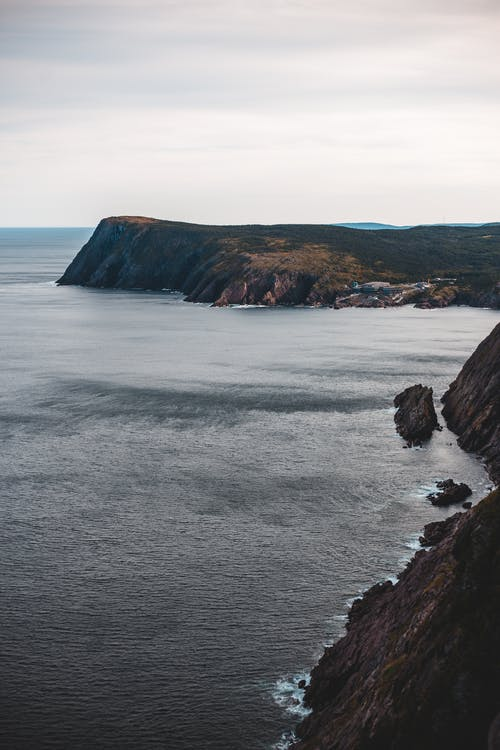From above scenic seascape of calm water surface surrounded by rocky cliffs in cloudy day
