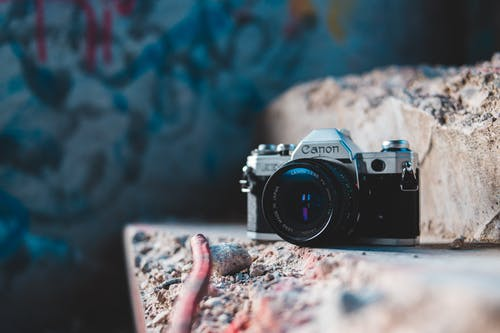 Old fashioned retro photo camera with lens on rough stone ribbed texture at daytime
