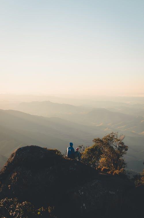2 People Sitting on Rock Mountain