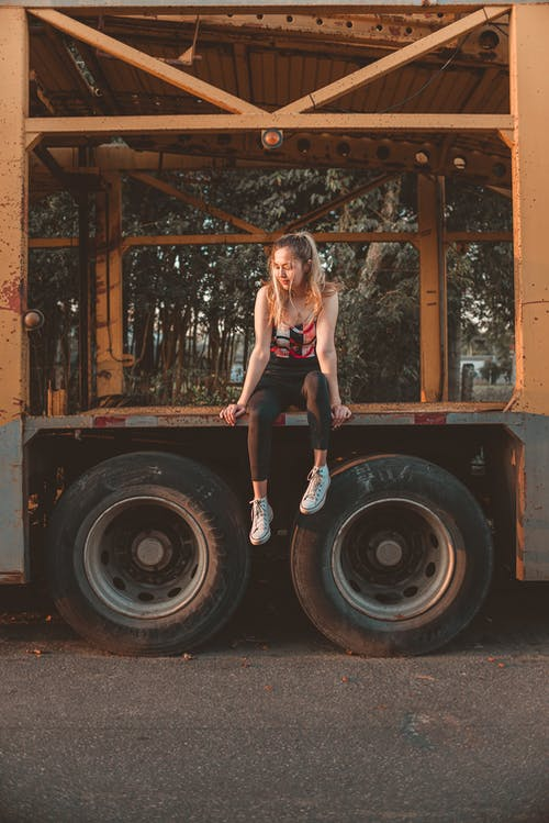 Woman in Pink Sports Bra and Black Shorts Standing on Truck