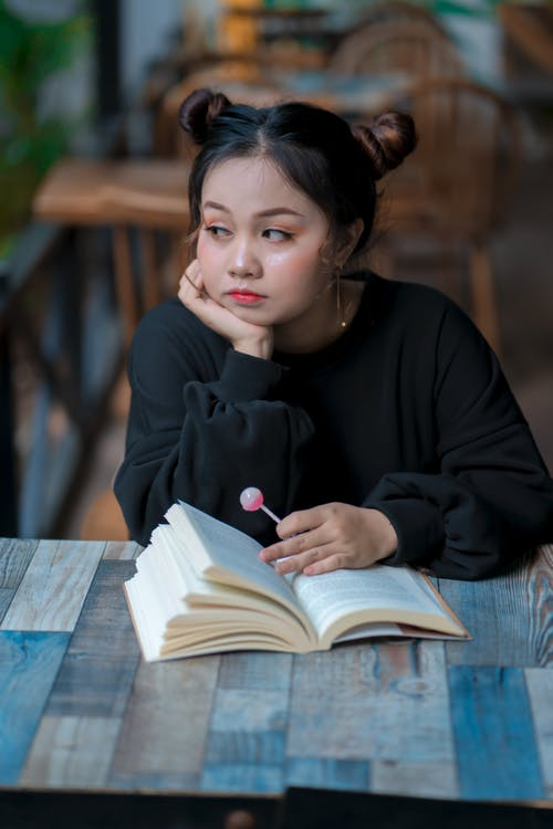 Thoughtful young ethnic teen student reading textbook in cafeteria