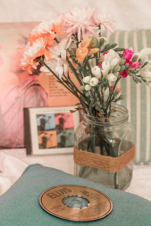 Bouquet of bright aromatic flowers in glass vase near disk and pictures on table