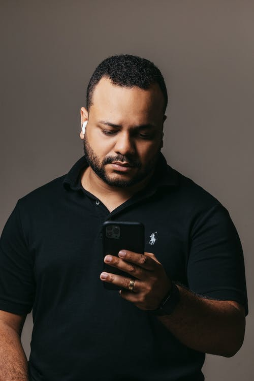 Serious ethnic male in black t shirt and headphones looking at modern smartphone while standing near gray wall