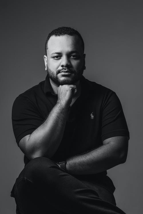 Black and white of confident bearded black male sitting on armchair and looking at camera thoughtfully