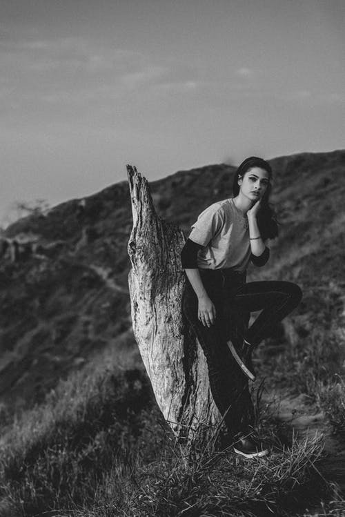 Black and white full body of unemotional female in casual clothing looking at camera while raising leg and leaning to old dry stump with hand at chin