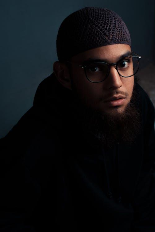 Pensive man in black coat and crochet taqiyah