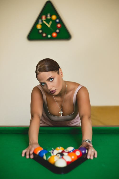 Woman in Brown Tank Top Sitting on Green and Yellow Billiard Table