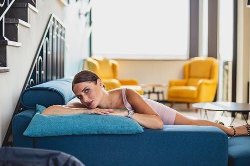 Woman in White Brassiere Lying on Blue Couch