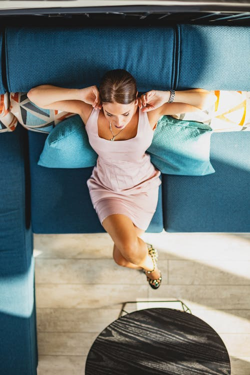 Woman in White Tank Top and Purple Shorts Sitting on Blue Couch