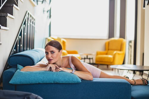 Woman in Blue Tank Top Lying on Blue Couch
