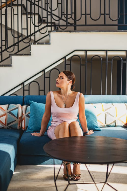 Woman in Pink Spaghetti Strap Top Sitting on Blue Couch