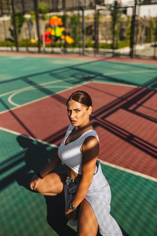 Woman in White Tank Top and Black Shorts Sitting on Tennis Court