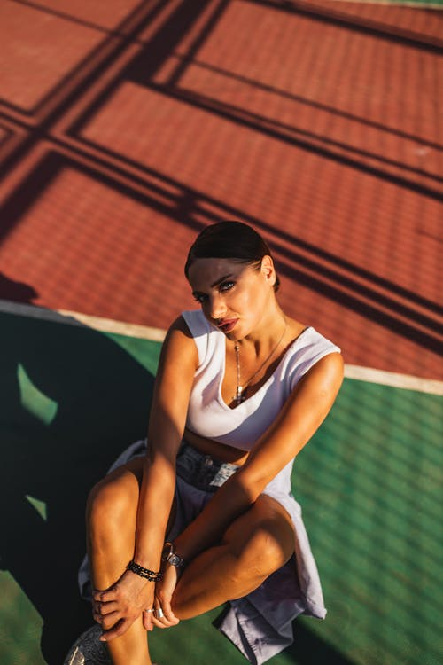 Woman in White Tank Top and Blue Denim Shorts Sitting on Tennis Court