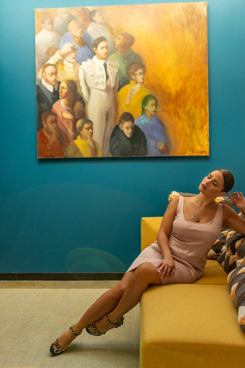 Woman in White Sleeveless Dress Sitting on Blue Couch