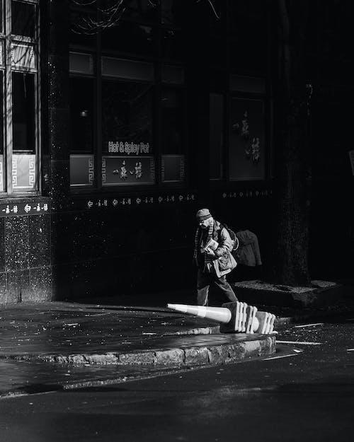 Grayscale Photo of Man Sitting on Sidewalk