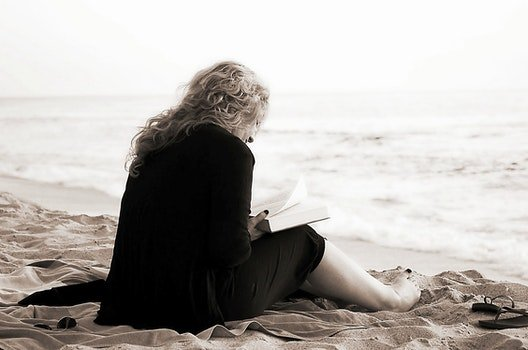 Person Sitting on the Seashore While Reading a Book