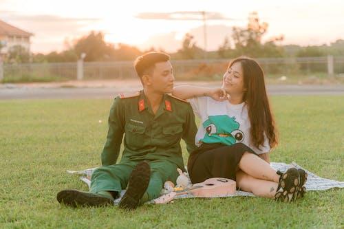 Woman in Green Uniform Sitting Beside Boy in Green Uniform on Grass Field