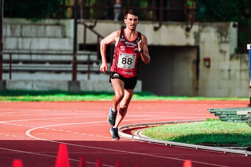 Full body of focused fit sportsman running on track during competition on stadium