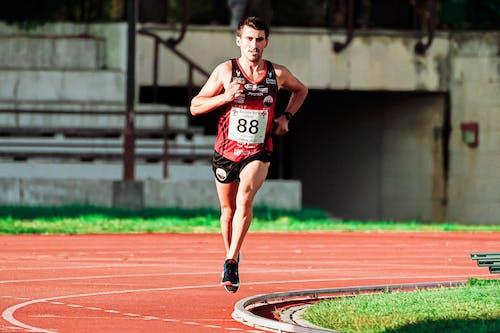 Determined sportsman running fast on stadium