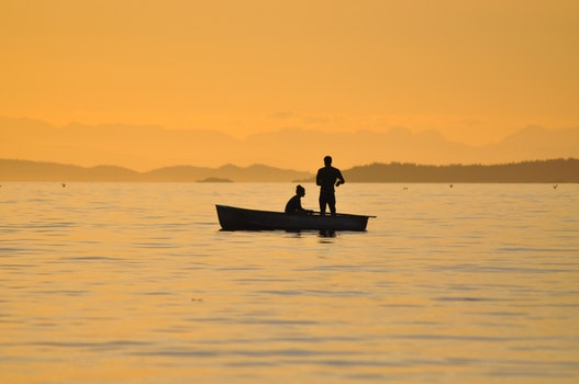2 People Standing Sitting in a Boat on Body of Water