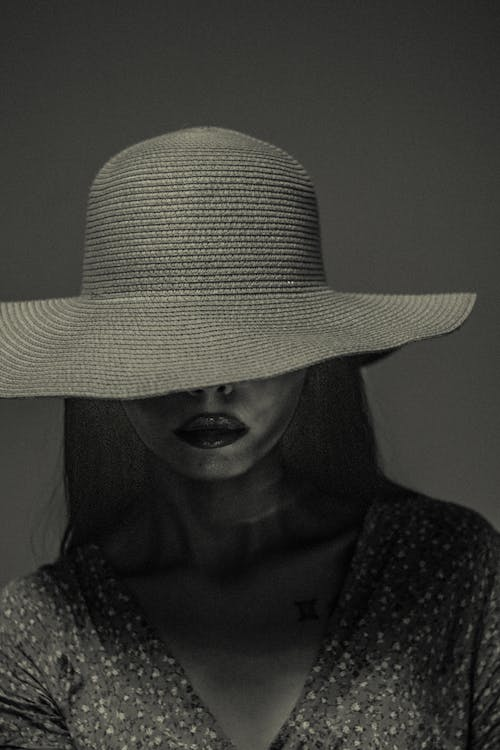 Calm woman in hat covering face