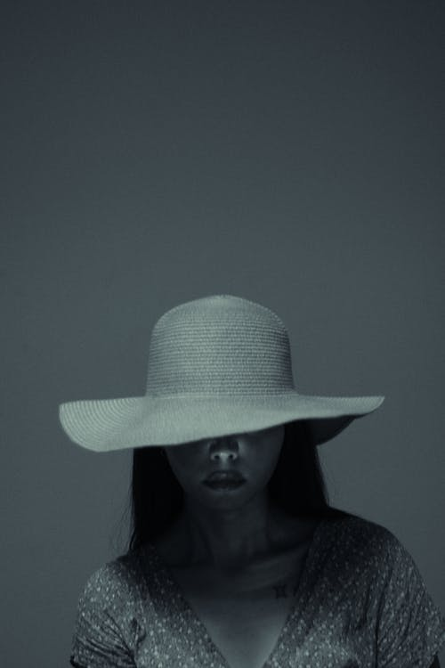 Woman in hat covering sad face