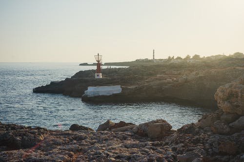 Lighthouse on rocky shore near endless sea in evening