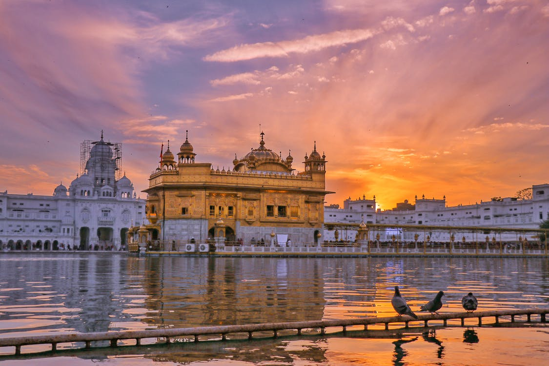 Exterior of Sikh gurdwara golden temple with dome located near water against cloudy sky in evening time in city in India