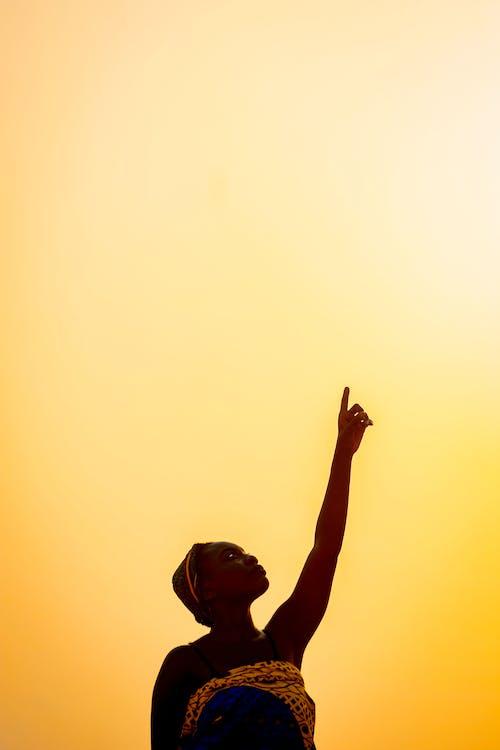 Black woman raising hand against skyline