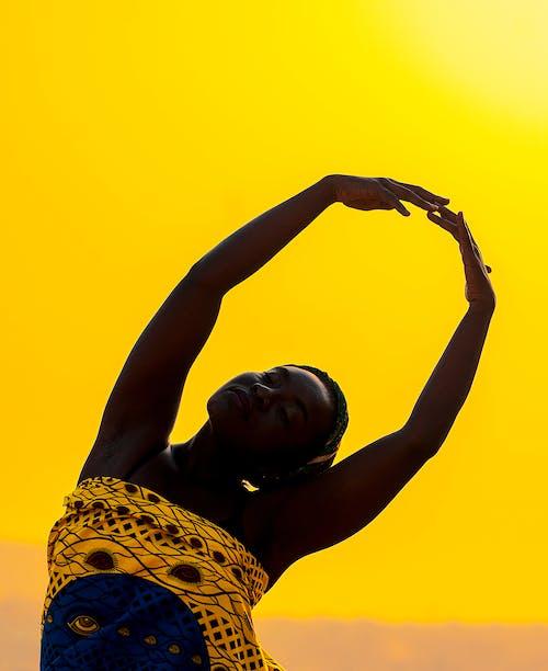 African woman dancing at sundown