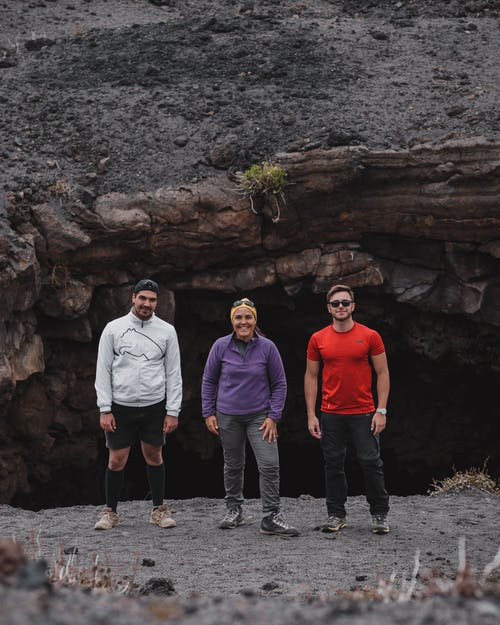 Group of multiethnic travelers in comfortable outfits standing on rocky slope near stone cave and looking at camera