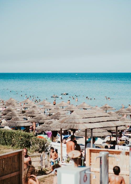 Tropical resort beach with deckchairs and sun umbrellas on sand near blue endless sea