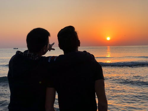 Friends standing near sea at sunset