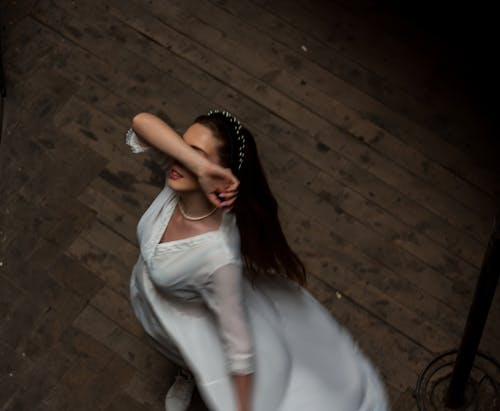 Elegant woman in white dress dancing in room