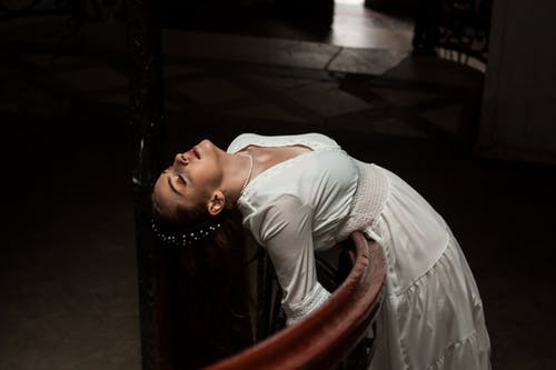 Graceful woman in dress leaning on railing