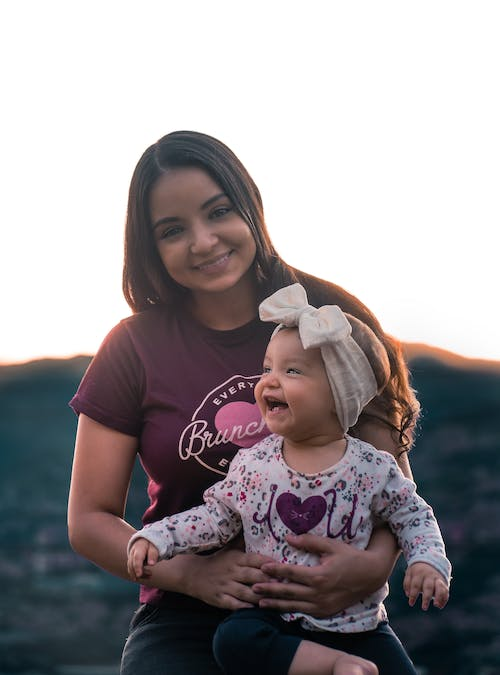 Cheerful ethnic woman looking at camera while hugging smiling little girl with headband in countryside with hill on blurred background