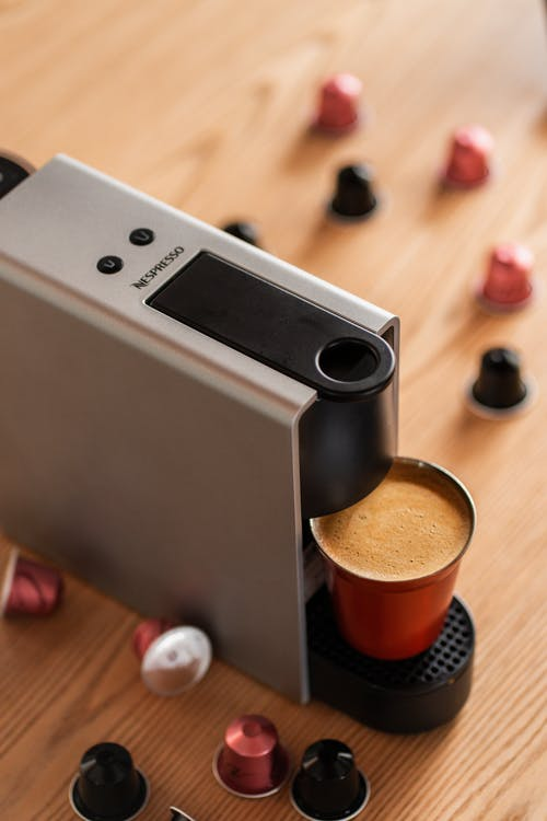 From above of modern automatic capsule coffee maker with cup of fresh hot drink placed on wooden counter in kitchen