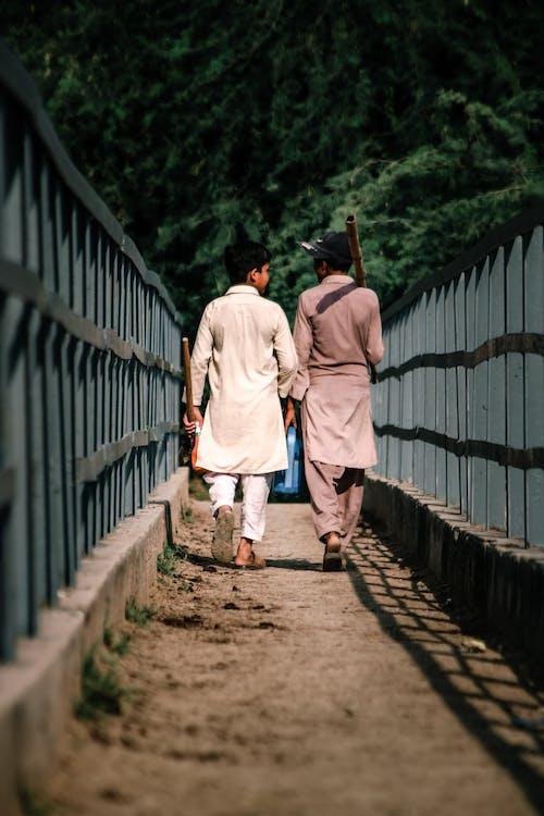 Man in White Thobe Walking on Brown Wooden Bridge