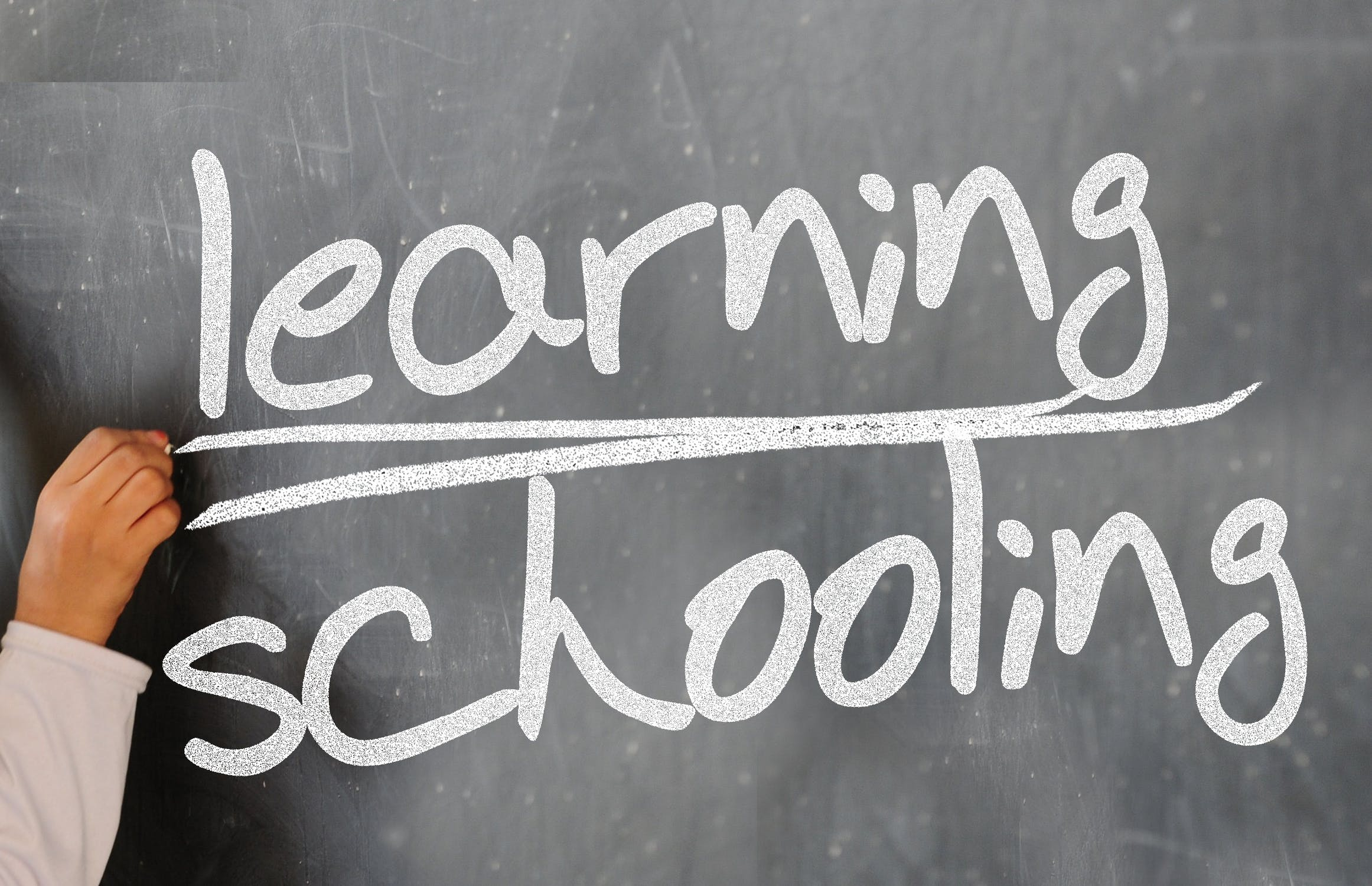 "Chalkboard with ""Learning Schooling"" written"