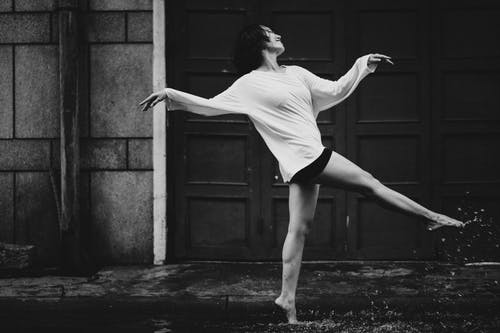 Black and white full body side view of barefoot female dancer walking happily in puddle on street